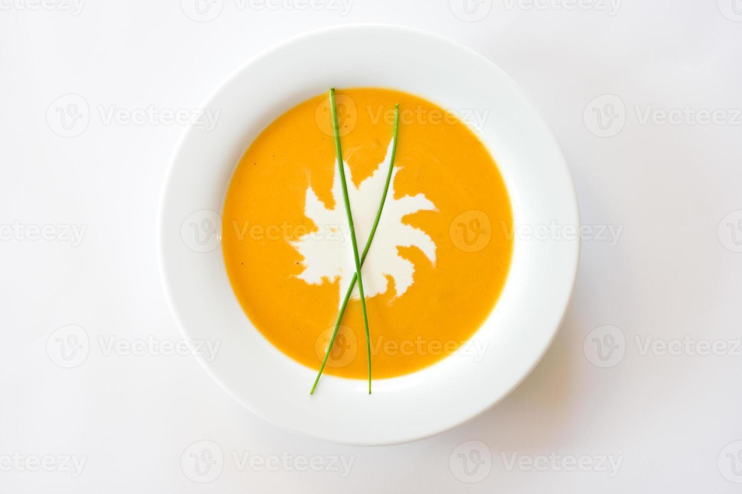 zuppa di zucca con macchia di panna ed erba cipollina foto