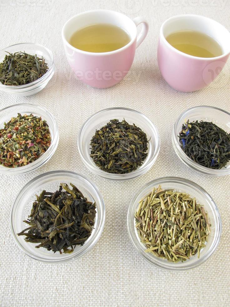 varietà di tè verde e due tazze di tè foto