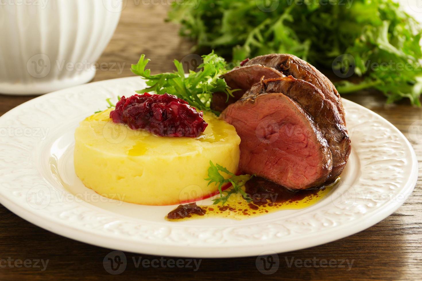 vitello arrosto con purè di patate e chutney di prugne. foto