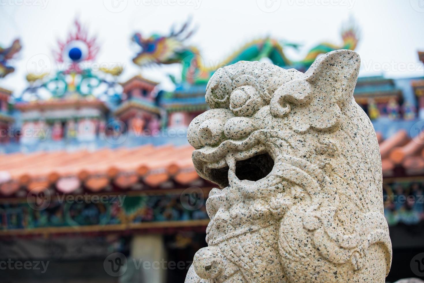 leone di pietra cinese con sfocatura dello sfondo del tempio foto
