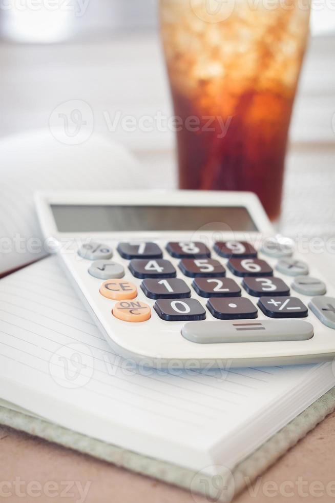 calcolatrice sul taccuino in bianco con un bicchiere di cola foto