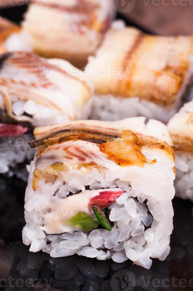 Rotolo di sushi di anguilla unagi su fondo di legno foto