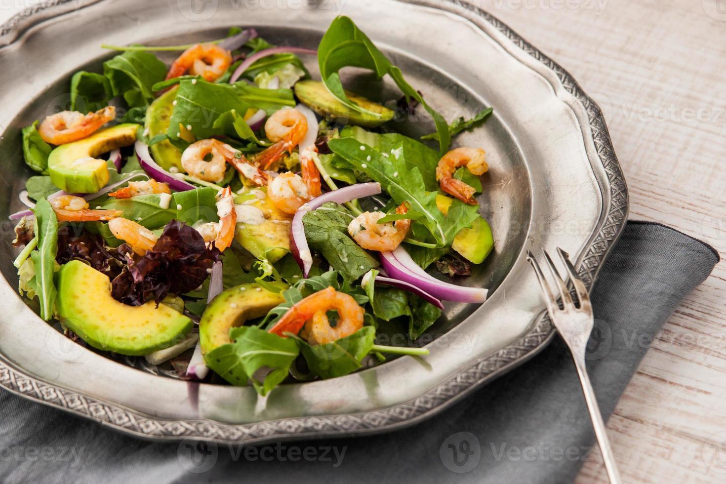 gamberi e insalata di avocado su piastra metallica vintage con forchetta foto