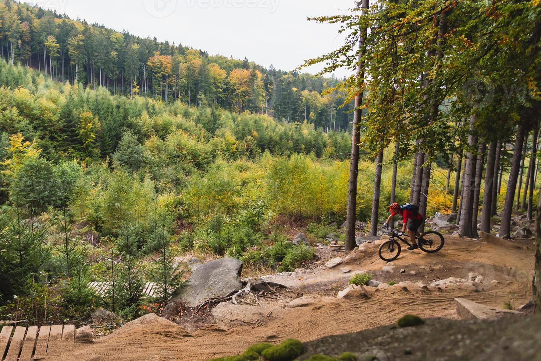 mountain bike equitazione in bicicletta nella foresta di autunno foto