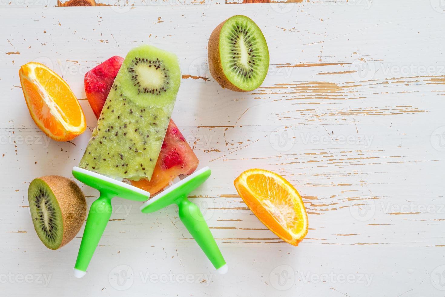 Schiocchi di ghiaccio di kiwi e frutti di bosco, fette d'arancia foto