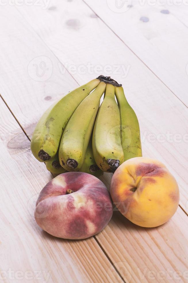 frutta sul tavolo di legno. banane, pesche e paraguayane foto