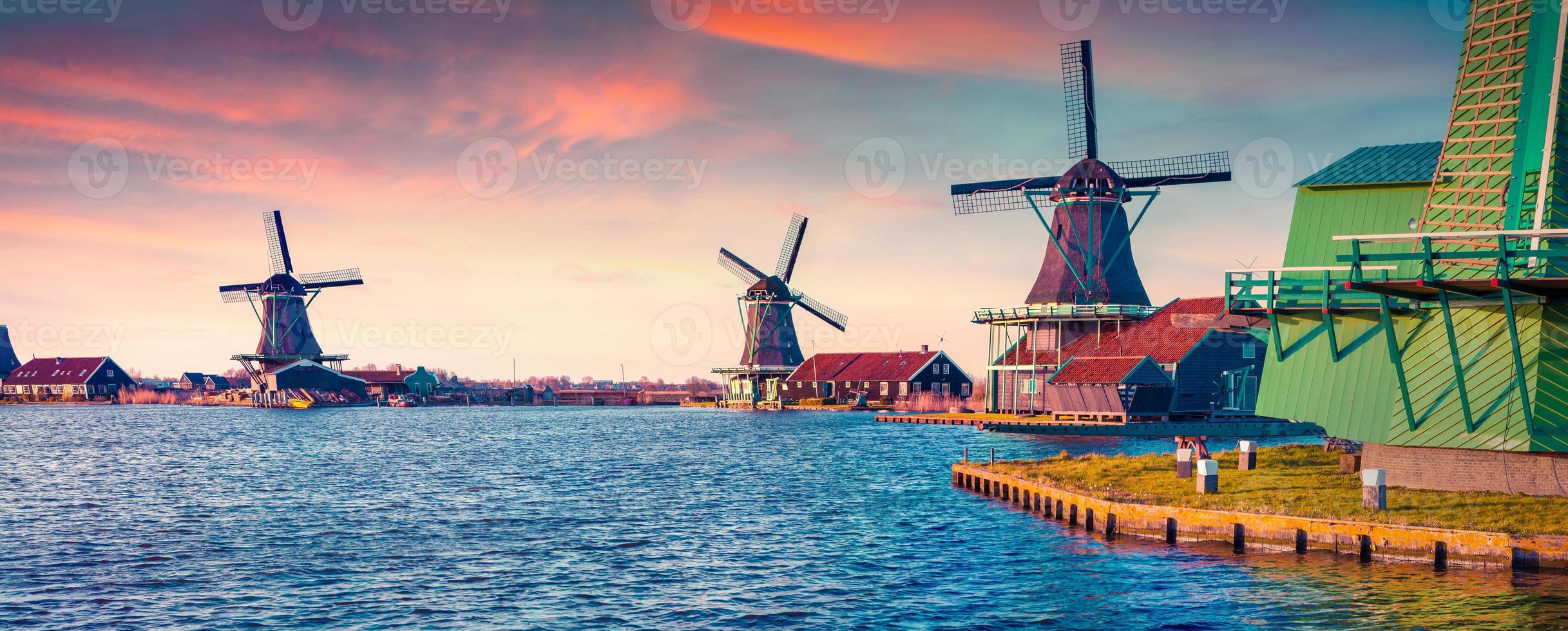 panorama di autentici mulini zaandam sul canale d'acqua foto