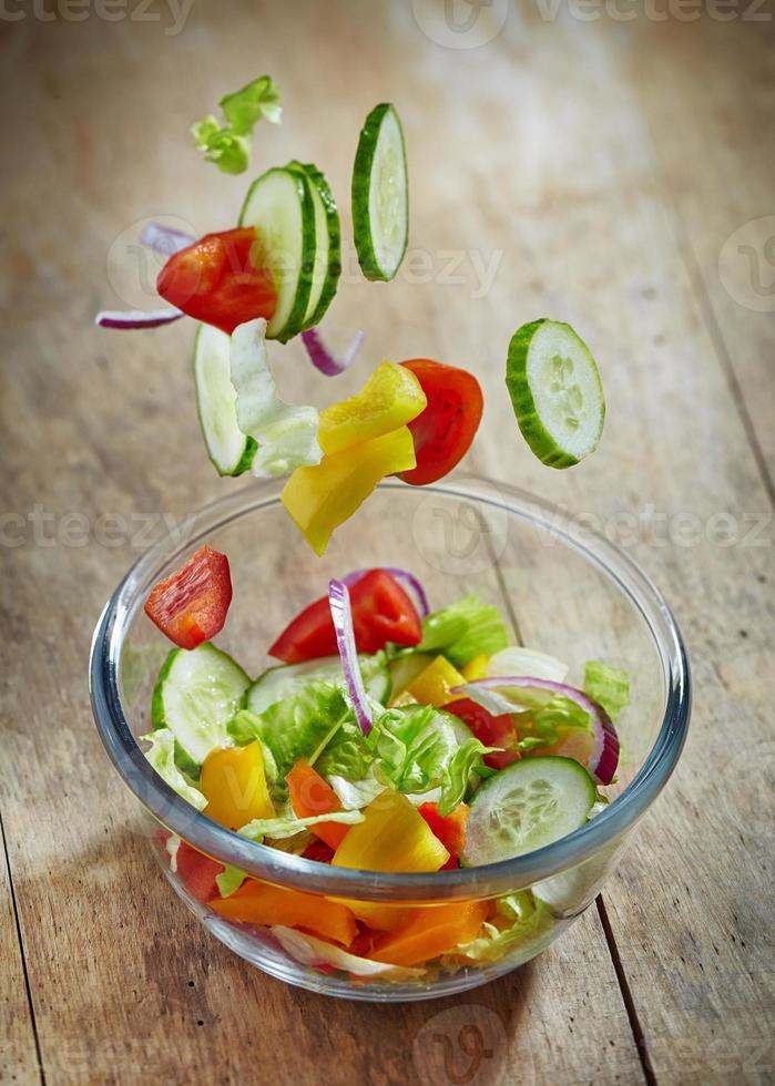 verdure fresche che cadono nella ciotola di vetro foto