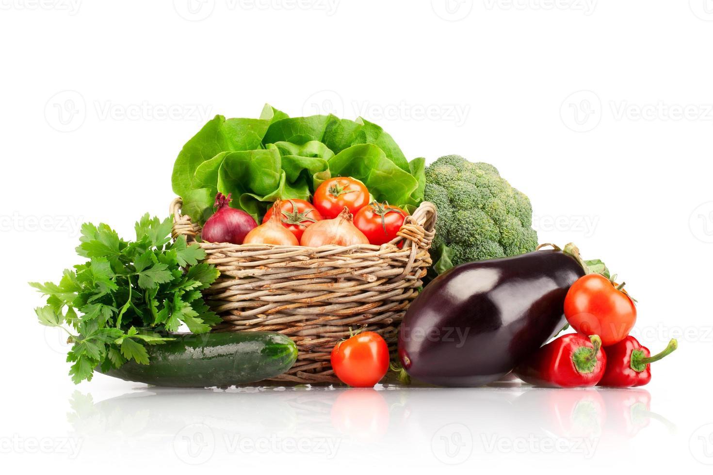 le verdure hanno organizzato in un cestino su una priorità bassa bianca foto