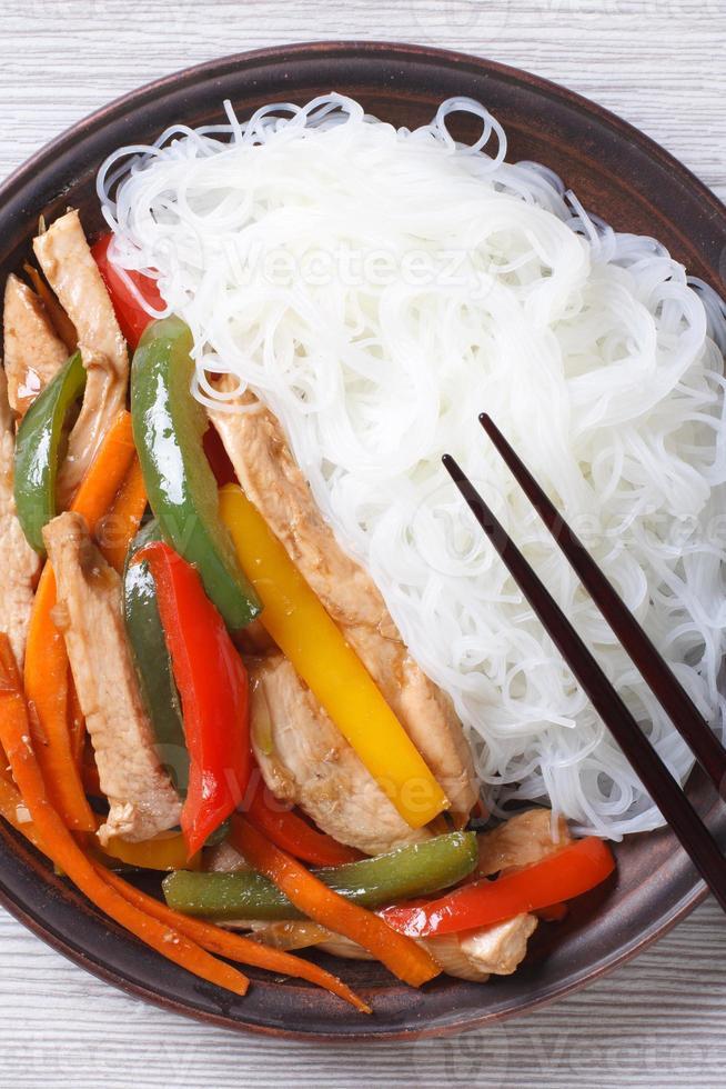 spaghetti di riso con macro di pollo, vista dall'alto verticale foto