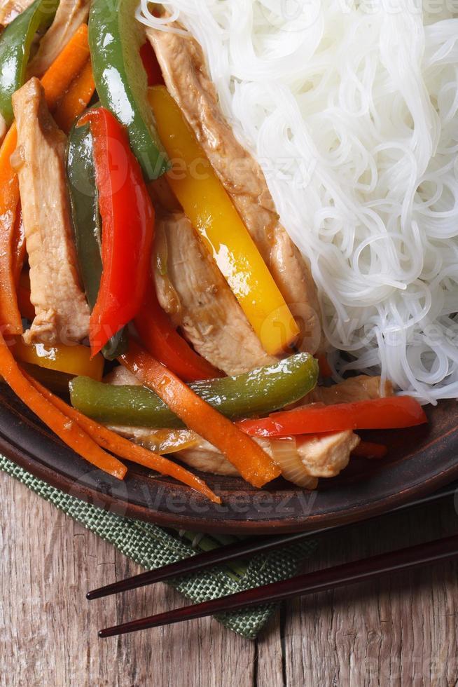 pollo asiatico dell'alimento con la macro vista superiore verticale delle tagliatelle di riso foto