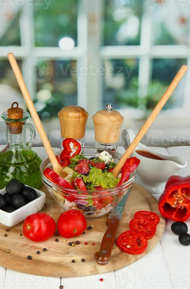 insalata greca fresca e ingredienti per cucinare sul tavolo foto