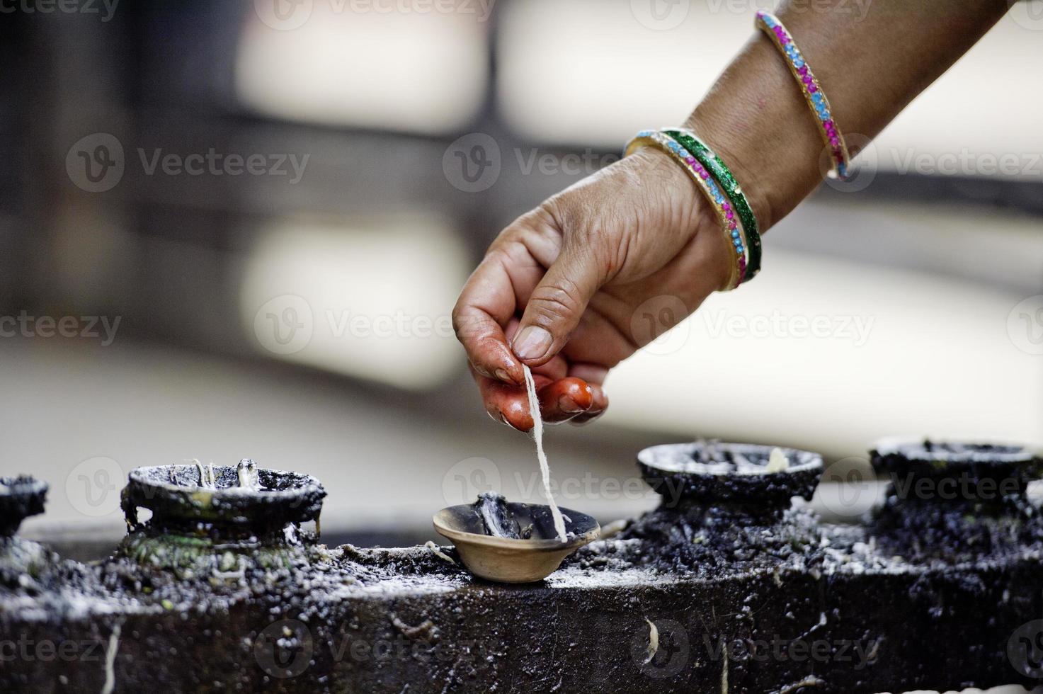 la donna accende le candele di burro di incenso foto