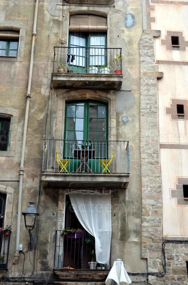 balcone con sedie gialle e bottiglie di vino foto