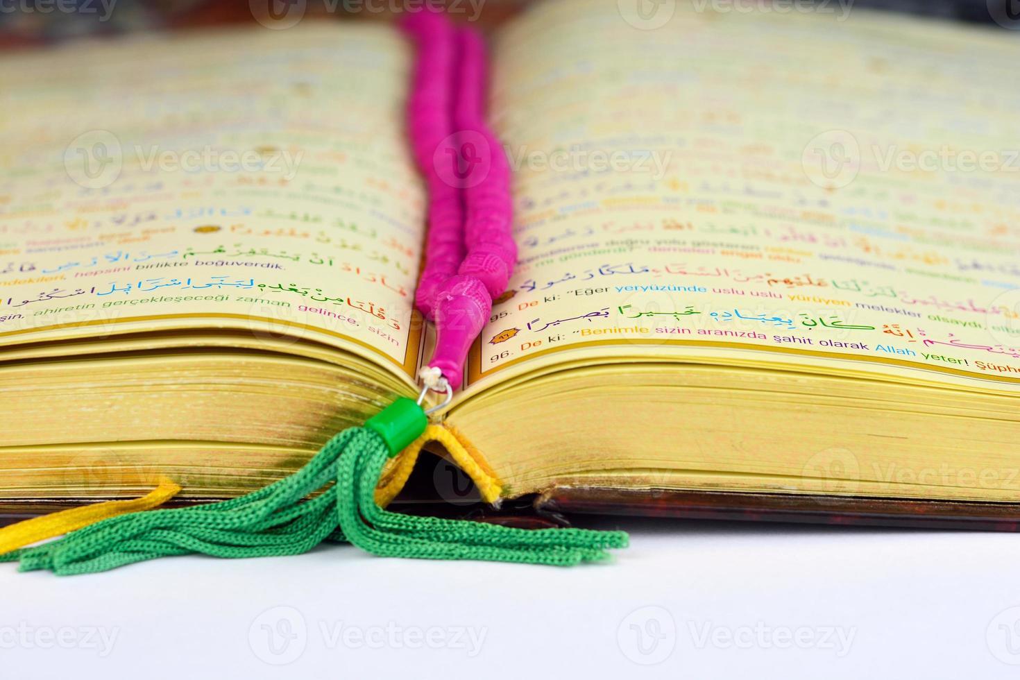 corano con rosario pregando perline a colori e pagine dorate foto