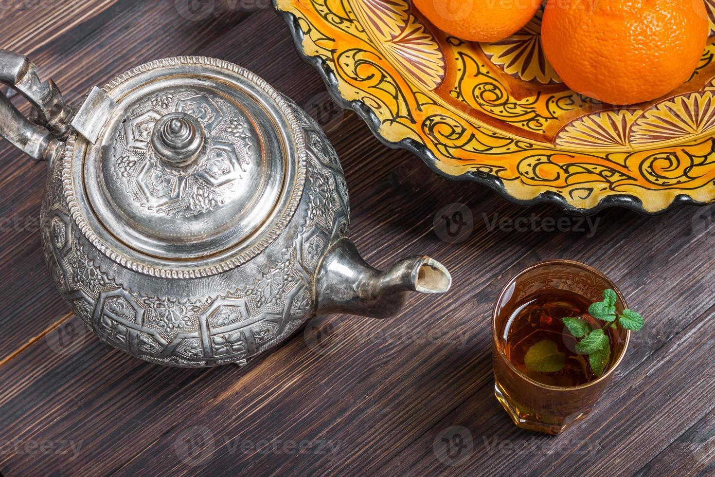 tè marocchino alla menta, bollitore e piatto con ornamenti tradizionali foto