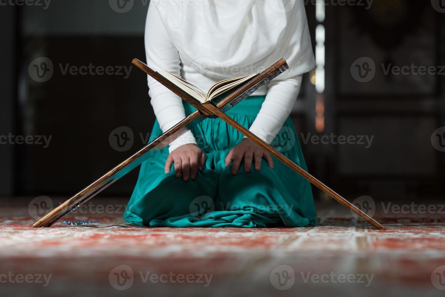 vicino donna musulmana sta leggendo il Corano foto