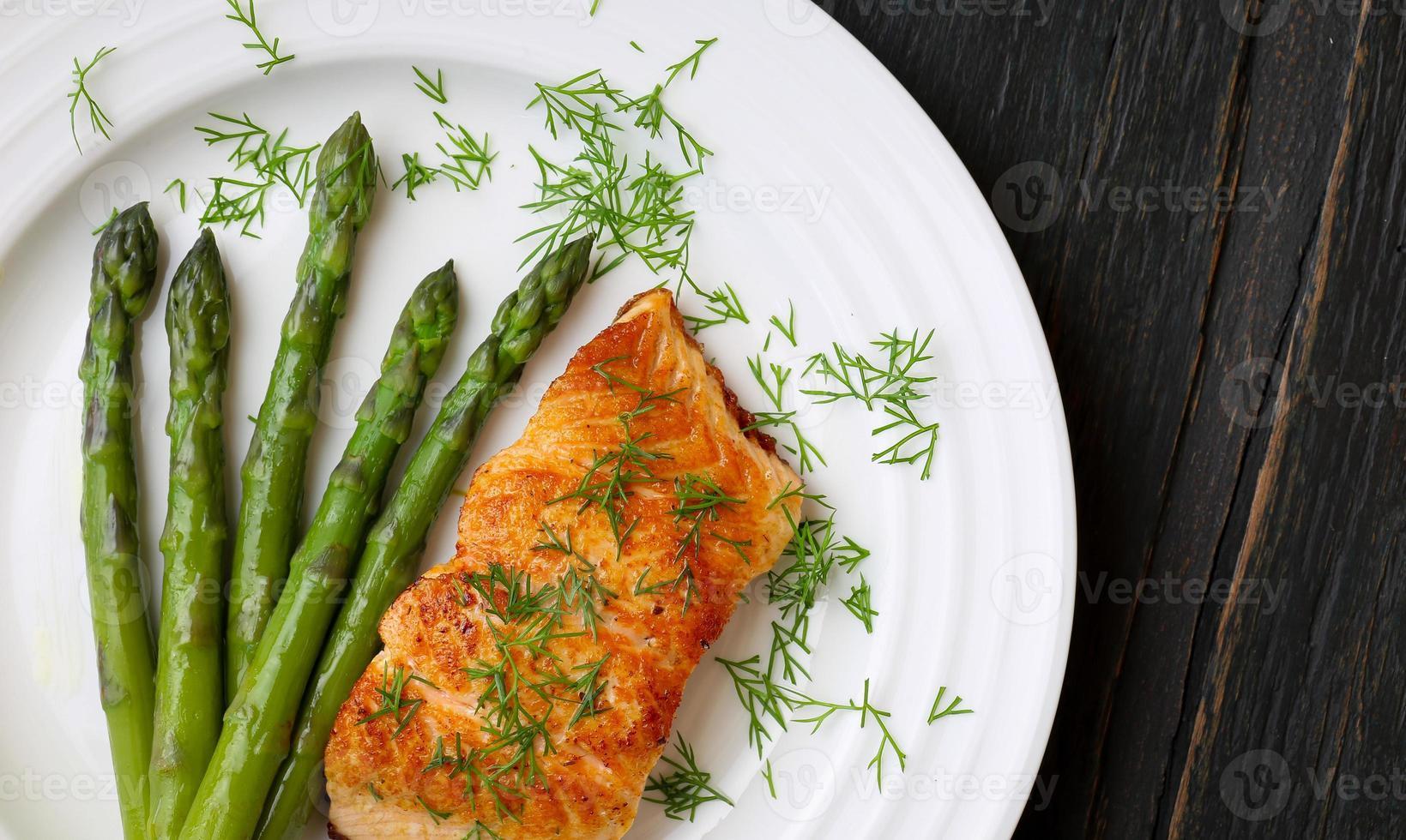 filetto di salmone con asparagi sul piatto bianco foto