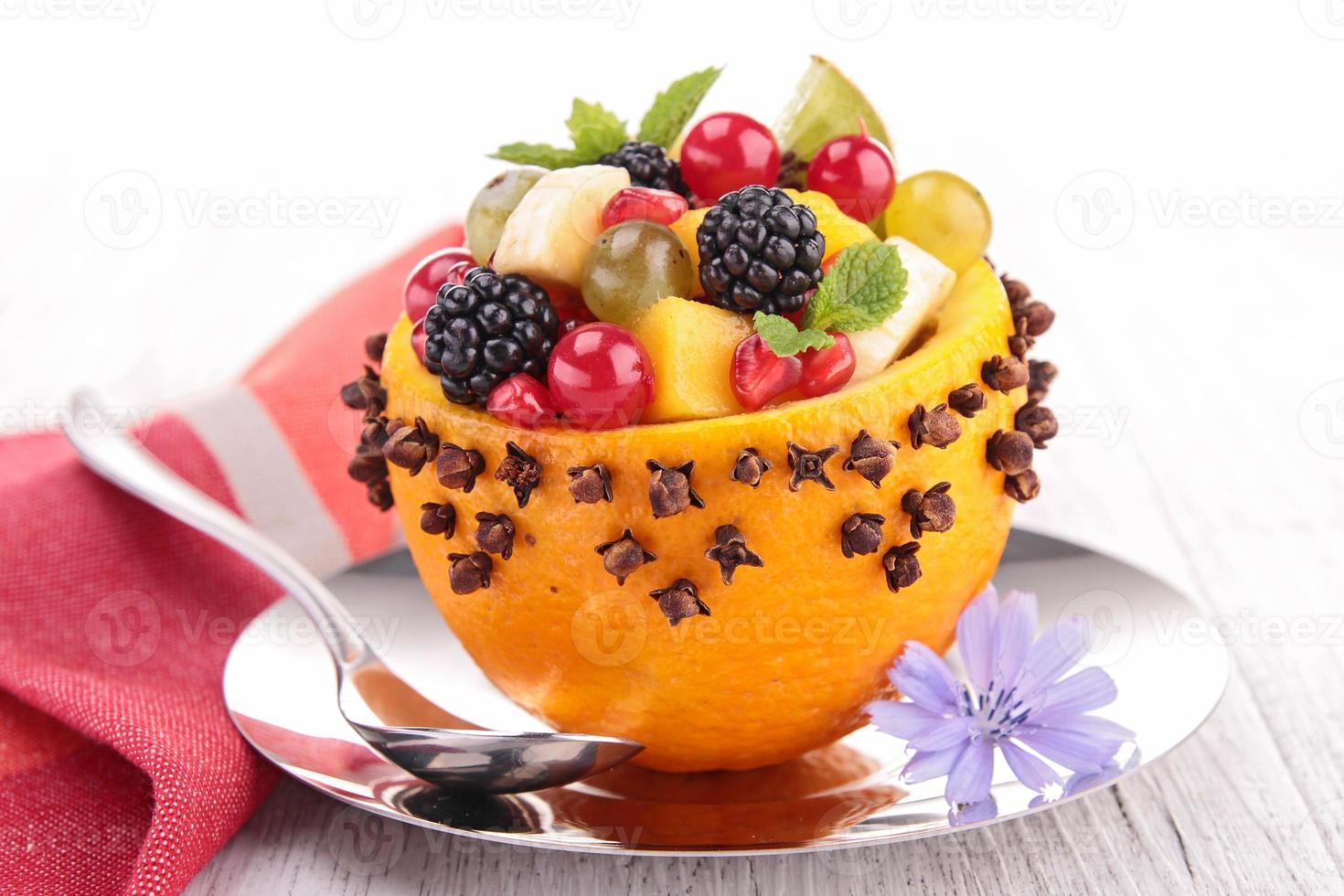 macedonia di frutta in una ciotola d'arancia foto