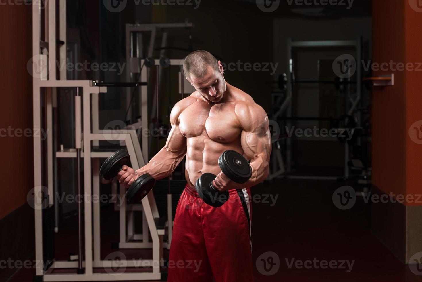 esercizio di bodybuilder con manubri foto