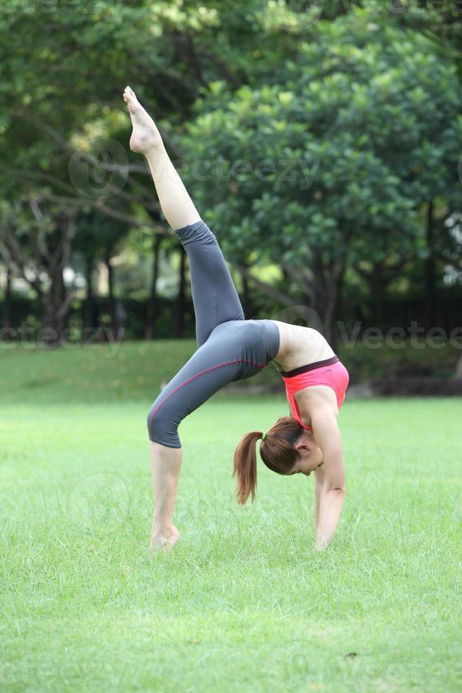 istruttore di yoga giovane e bella donna facendo ruota posa con uno foto