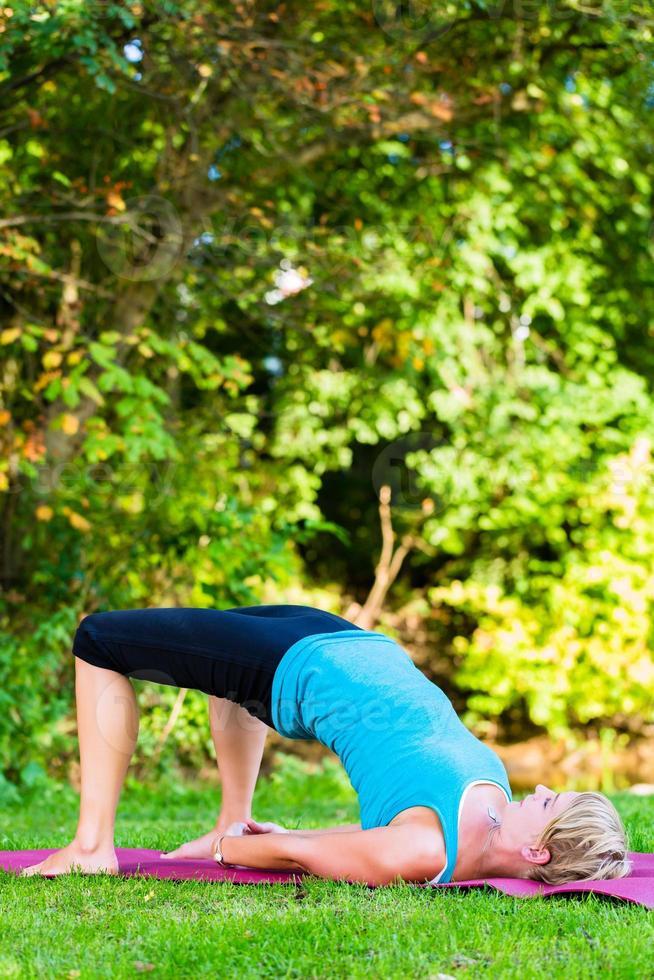 giovane donna in natura che fa yoga foto