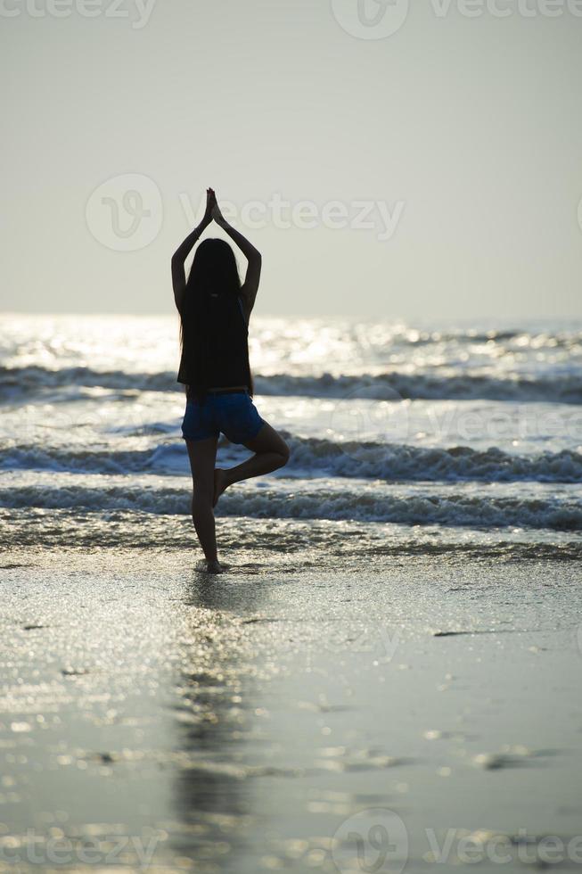 donna yoga sulla spiaggia foto