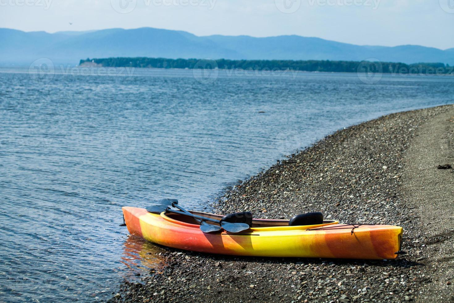 kayak arancione e giallo con remi in riva al mare foto