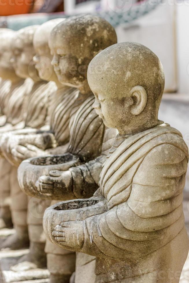 fila di monaci in stucco nel tempio. foto
