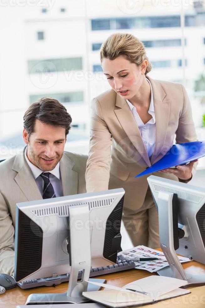 donna che mostra al suo collega qualcosa sullo schermo foto