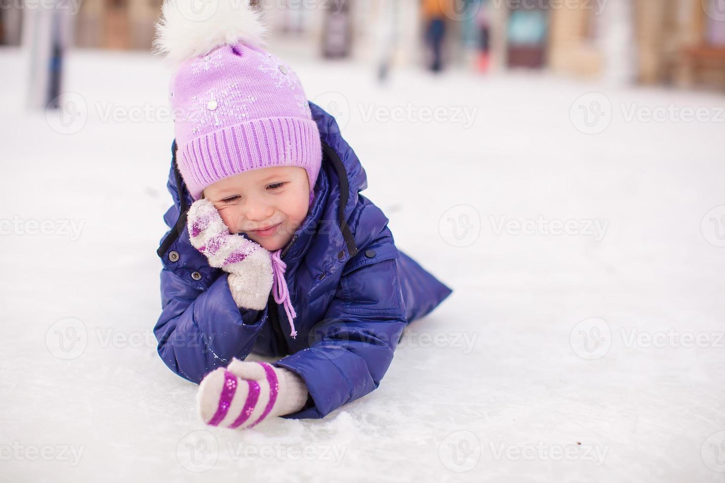 adorabile bambina posa sulla pista di pattinaggio dopo la caduta foto