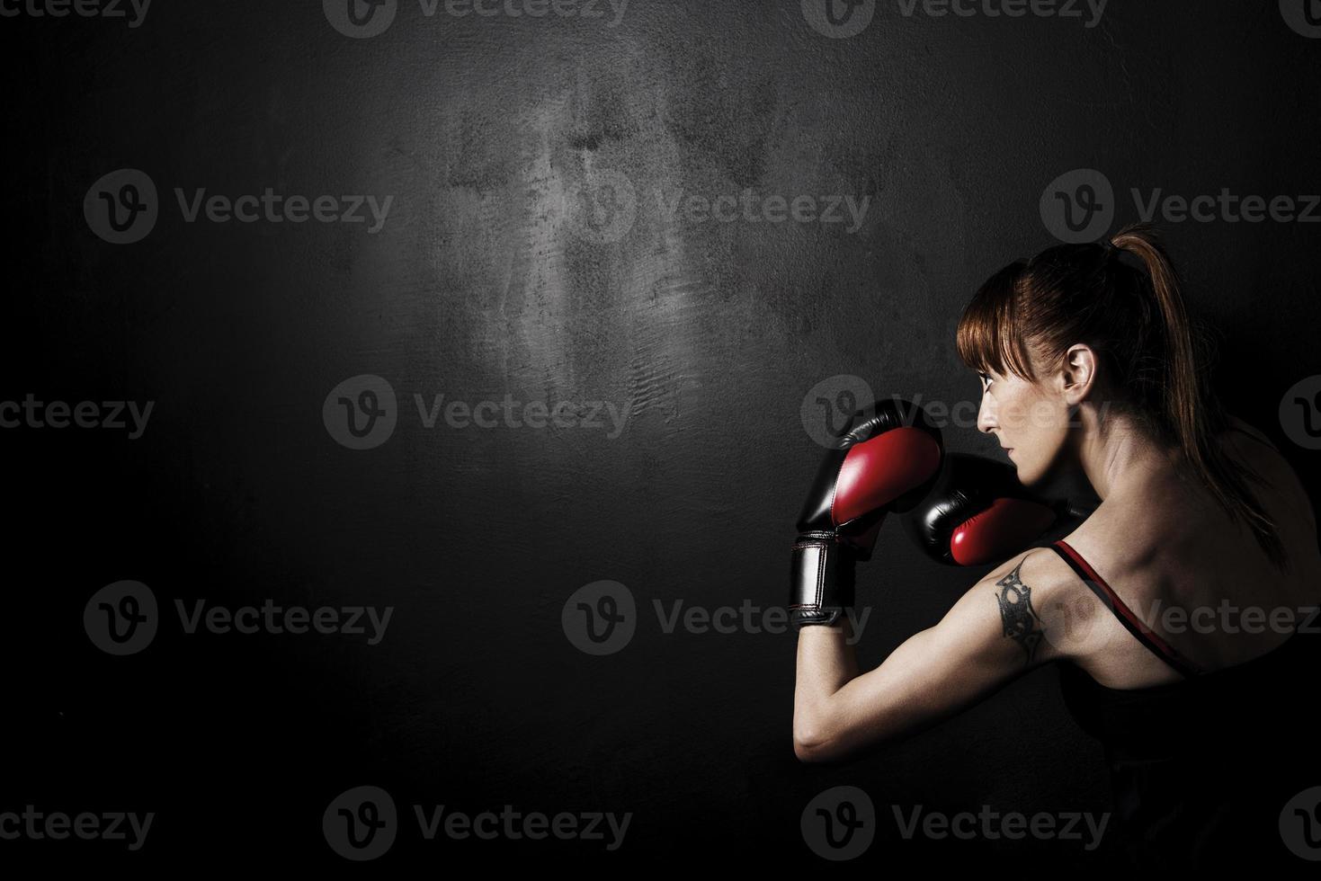 pugile della donna con i guanti rossi su backgroung nero foto