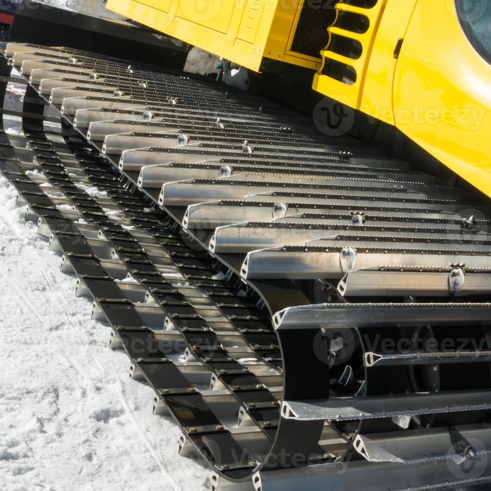 veicolo cingolato giallo sulla neve, macchina per toelettatura foto