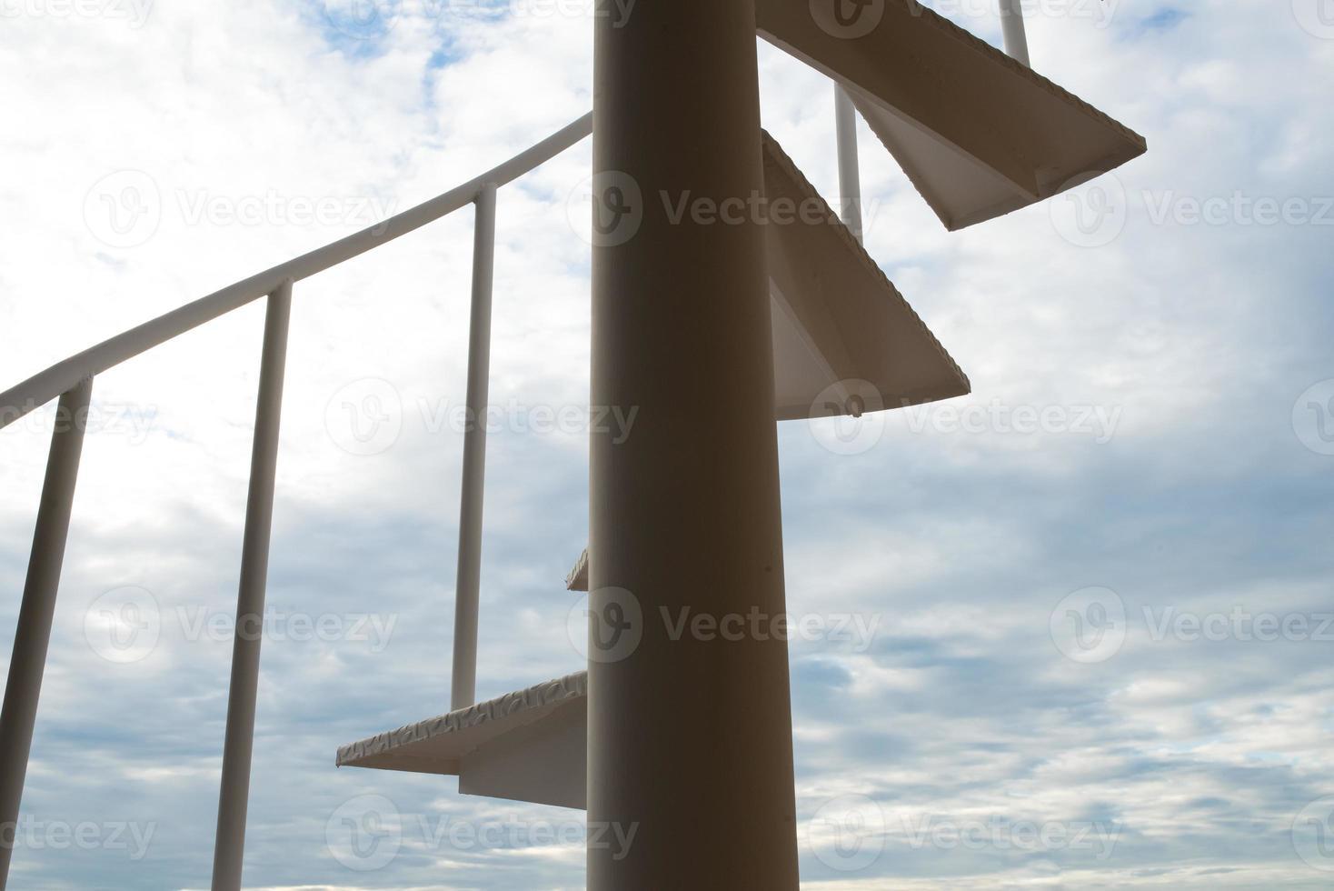 scala a chiocciola bianca sullo sfondo del cielo foto