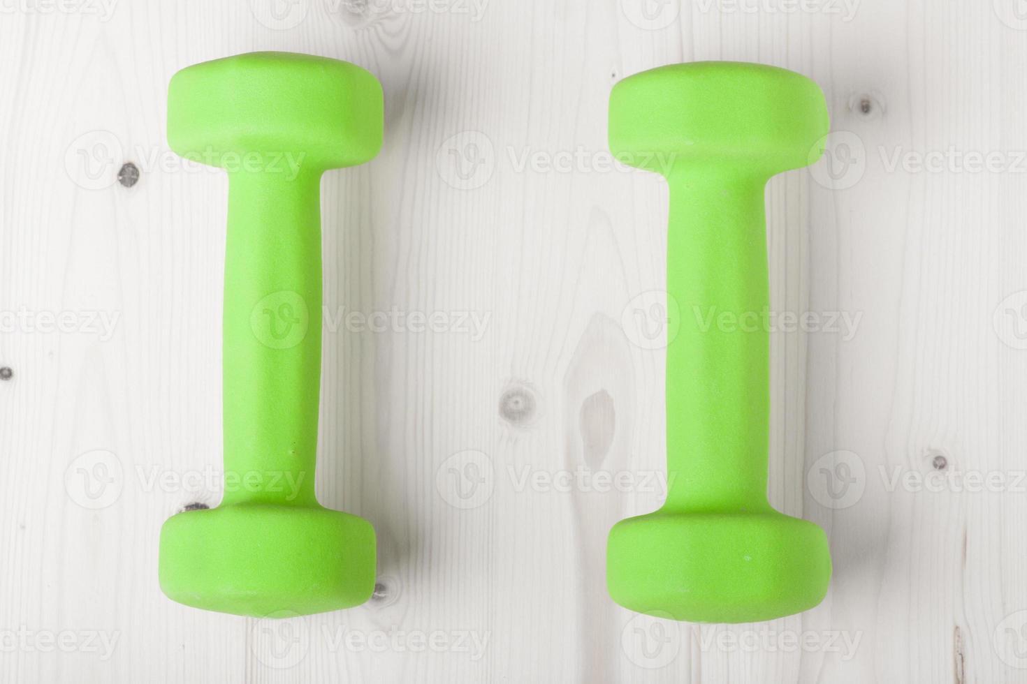 piccoli manubri verdi su superficie di legno foto