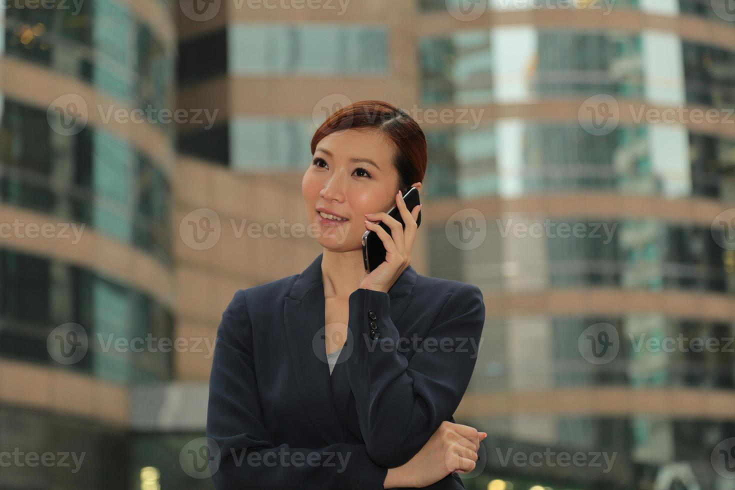 donne asiatiche di affari che per mezzo del suo smartphone foto