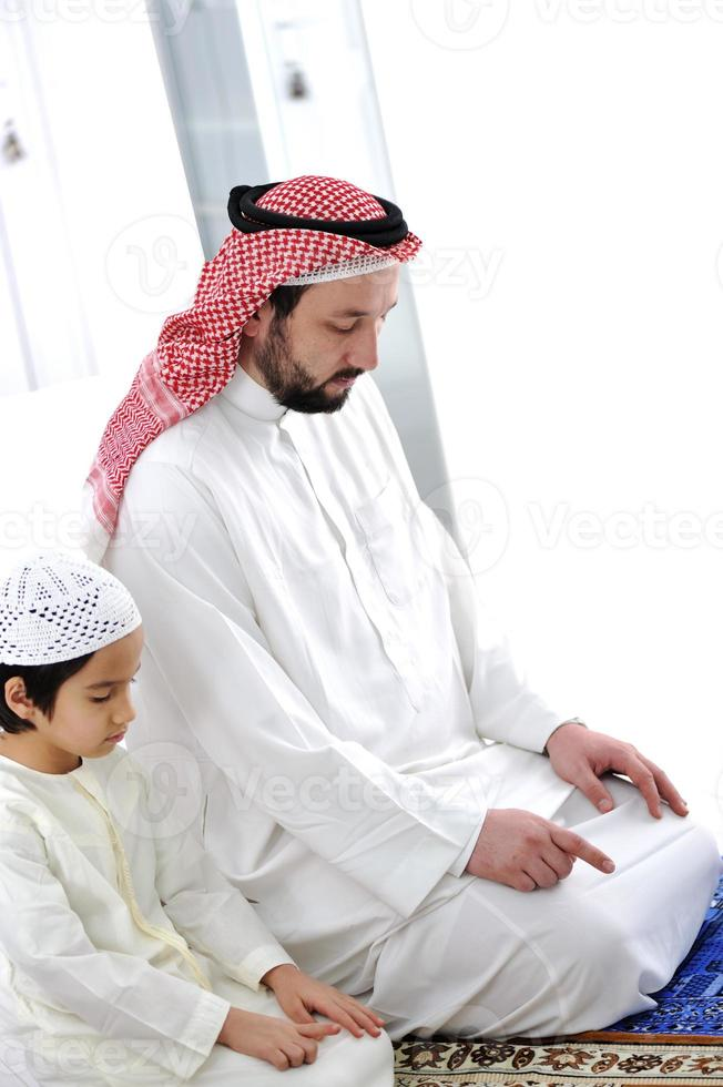 bambino arabo e insegnante che pregano insieme foto