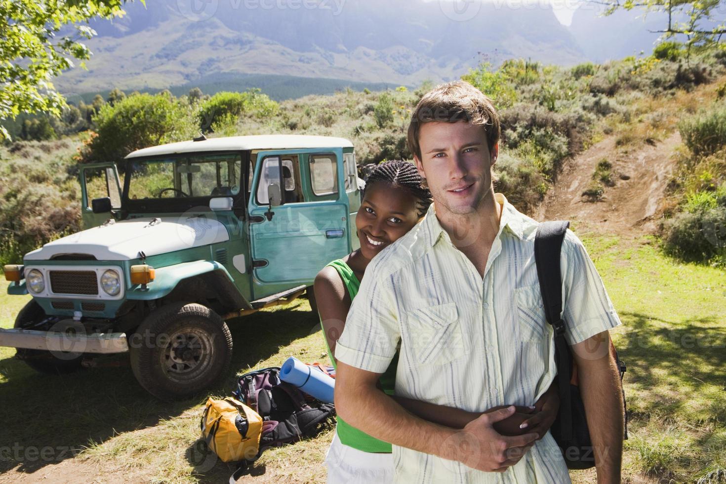 coppia vicino alla jeep parcheggiata all'inizio della vacanza in campeggio foto