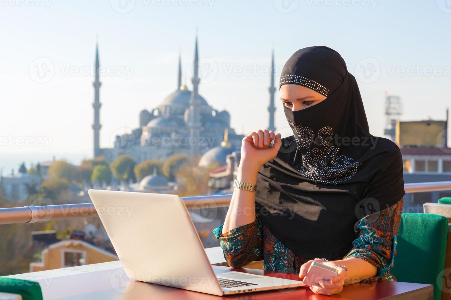 donna musulmana tradizionalmente vestita, lavorando sul computer foto