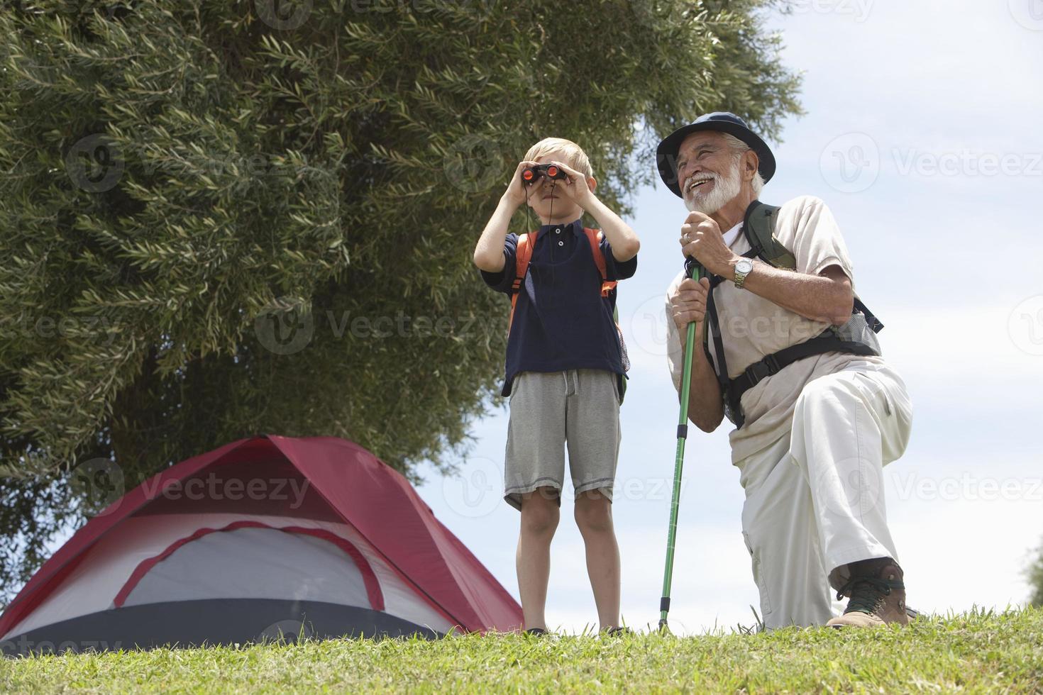 nonno e nipote bird watching davanti alla tenda foto