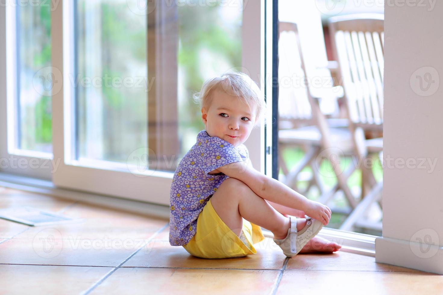 ragazza del bambino che mette le scarpe che si siedono sul pavimento accanto alla finestra foto