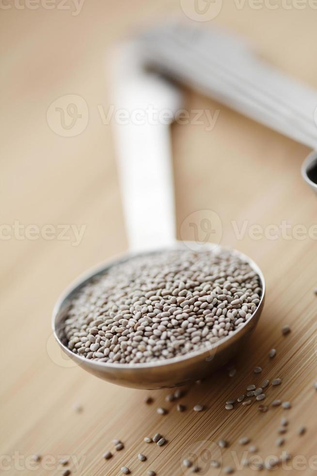 un cucchiaio da tavola pieno di semi di chia bianchi foto