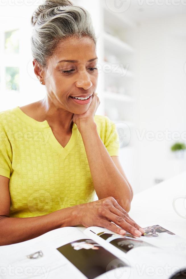 donna che mangia prima colazione e che legge rivista foto