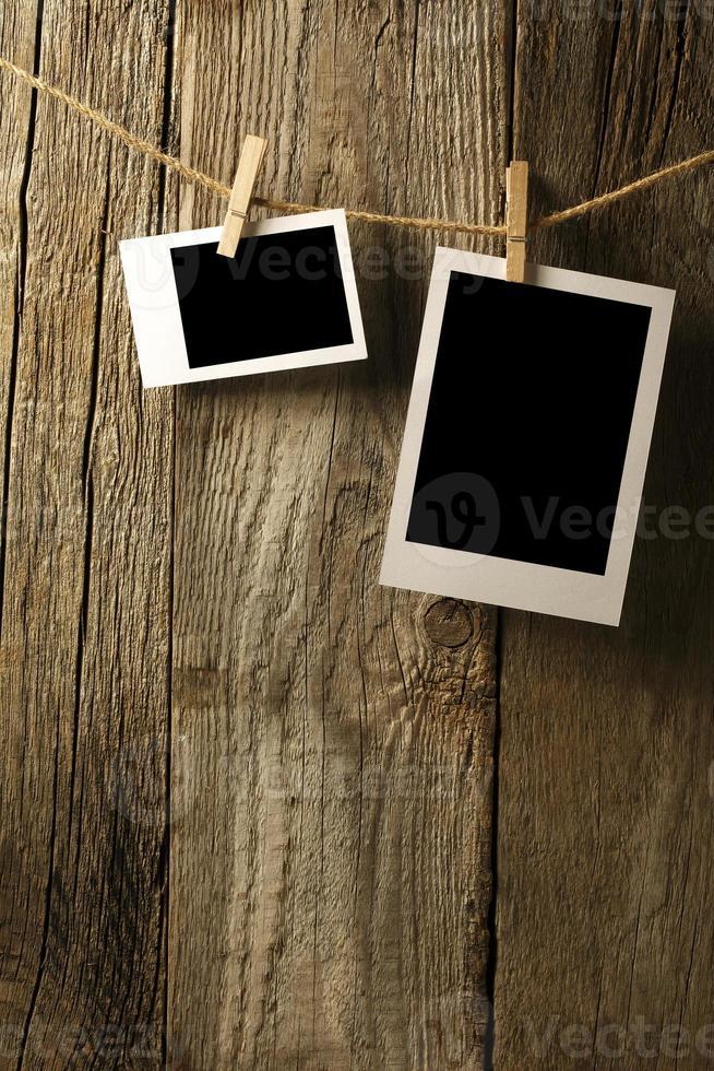 fotografie in bianco che appendono sulla vecchia parete di legno