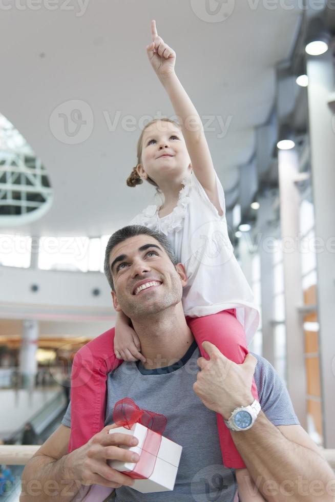 la giovane figlia indica e si siede sulle spalle dei padri foto