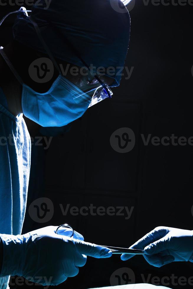 chirurghi che passano apparecchiature chirurgiche in sala operatoria, buio, primo piano foto