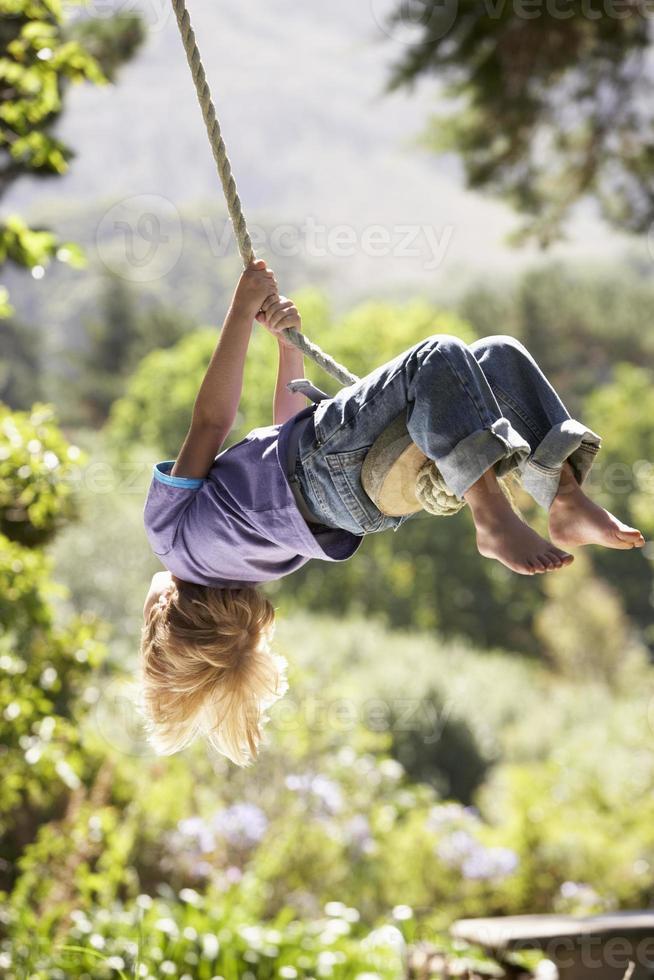 ragazzo che oscilla su una corda legata da un albero foto