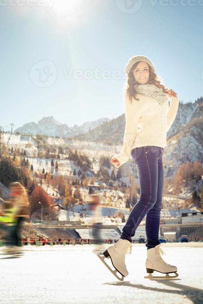 pattinaggio su ghiaccio grazioso della ragazza all'aperto alla pista di pattinaggio sul ghiaccio foto