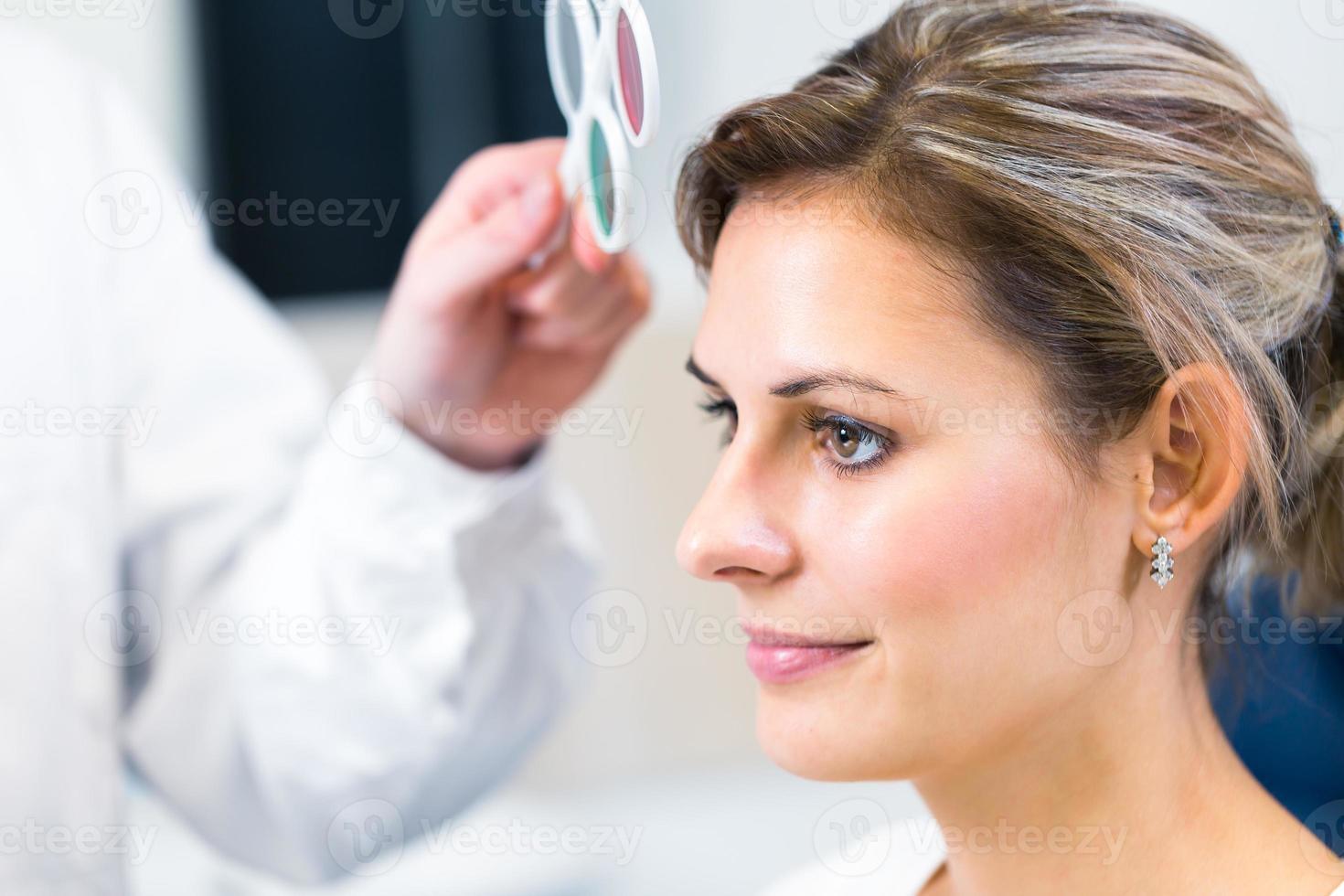 bella giovane donna che ha i suoi occhi esaminati da optometrici foto