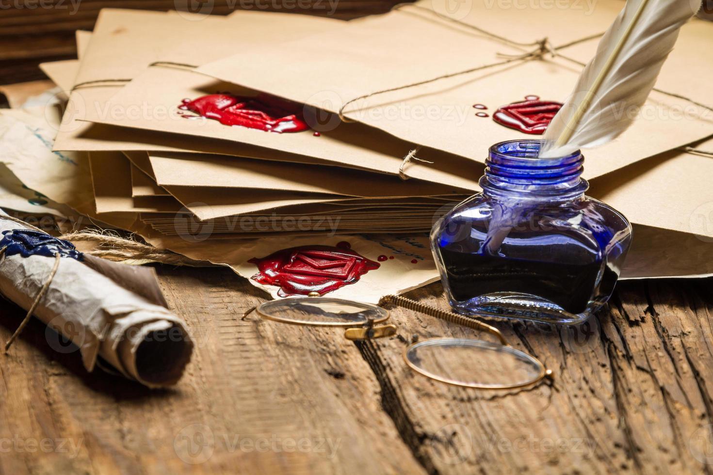 calamaio blu e bicchieri sul tavolo pieno di vecchi messaggi. foto